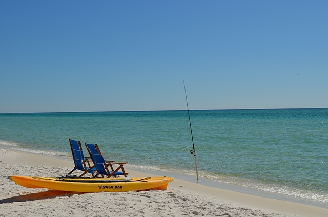 fishing pole and kayak on beach